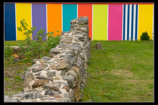 The old wall of an 1860's fort. Not sure about the multi colour wall behind.