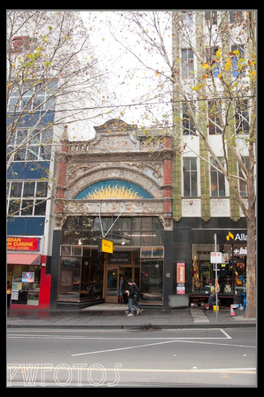 A lone single story building on Coliins Street is dwarfed by its neighbours