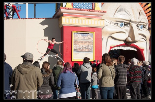 A street acrobat performs to the crowds outside of Luna Park in St Kilda