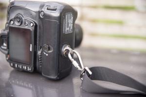 The strap attaches via the camera's tripod screw